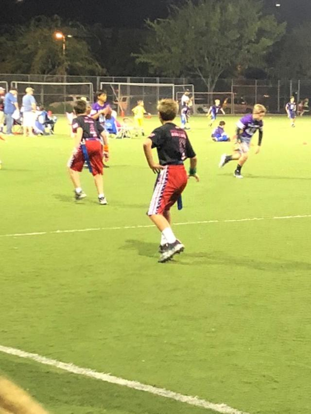 Exercise when sick: boy runs backward while playing in a flag football game