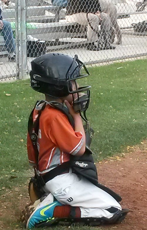 catcher: young baseball catching on his knees waiting for a game to start