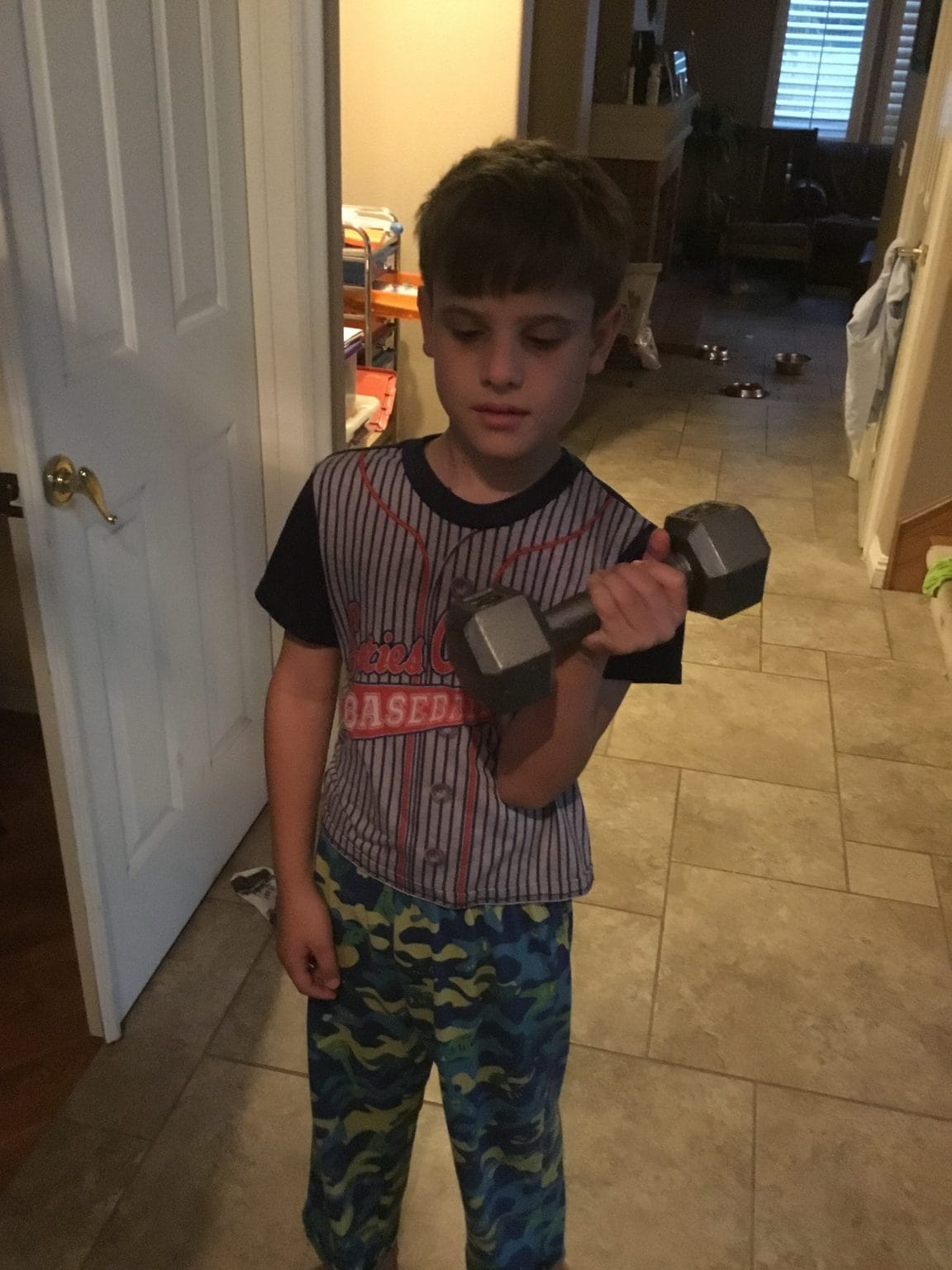 Strength Training- a young boy lifts a dumbbell