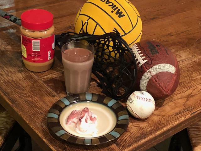 Protein: Picture of chocolate milk, yogurt and peanut butter next to a football, baseball and lacrosse stick